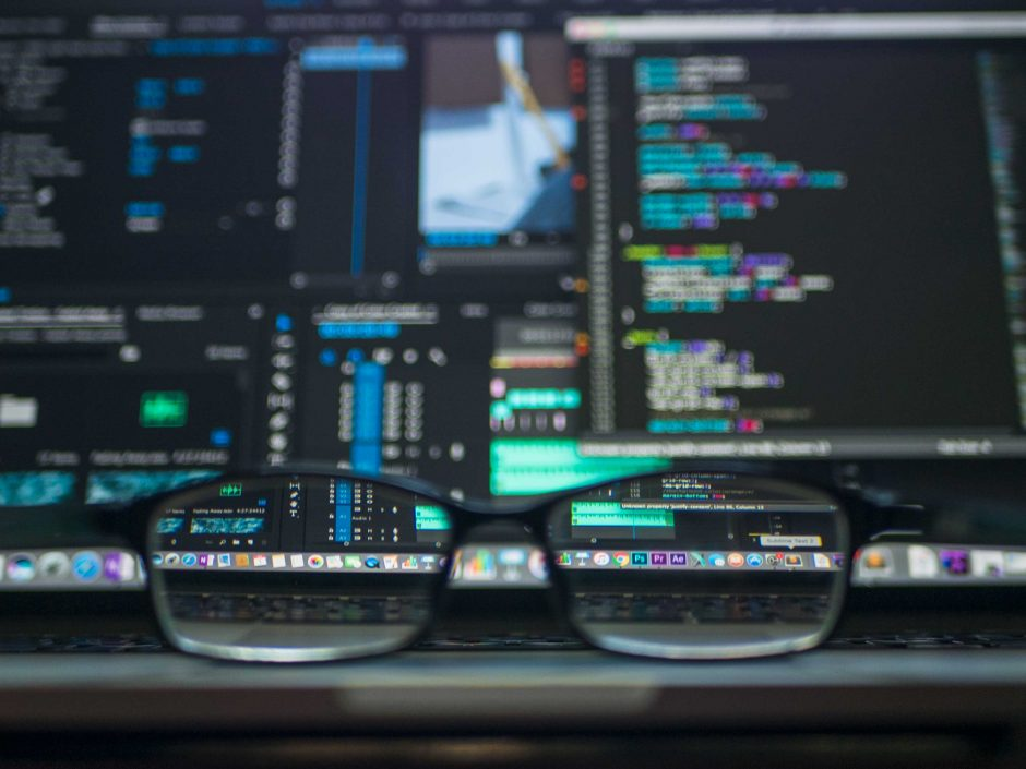 This is a photo of glasses in front of several computer monitors.