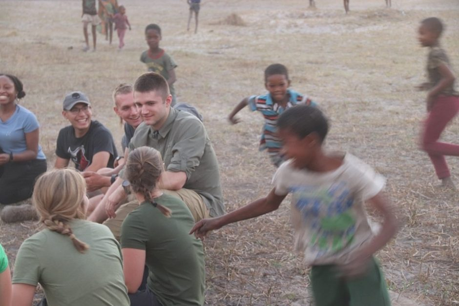 Benjamin Steger and his fellow cadets play duck-duck goose with children from an Botswanan tribe.