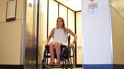 This is a picture of a student in a wheelchair exiting an elevator.