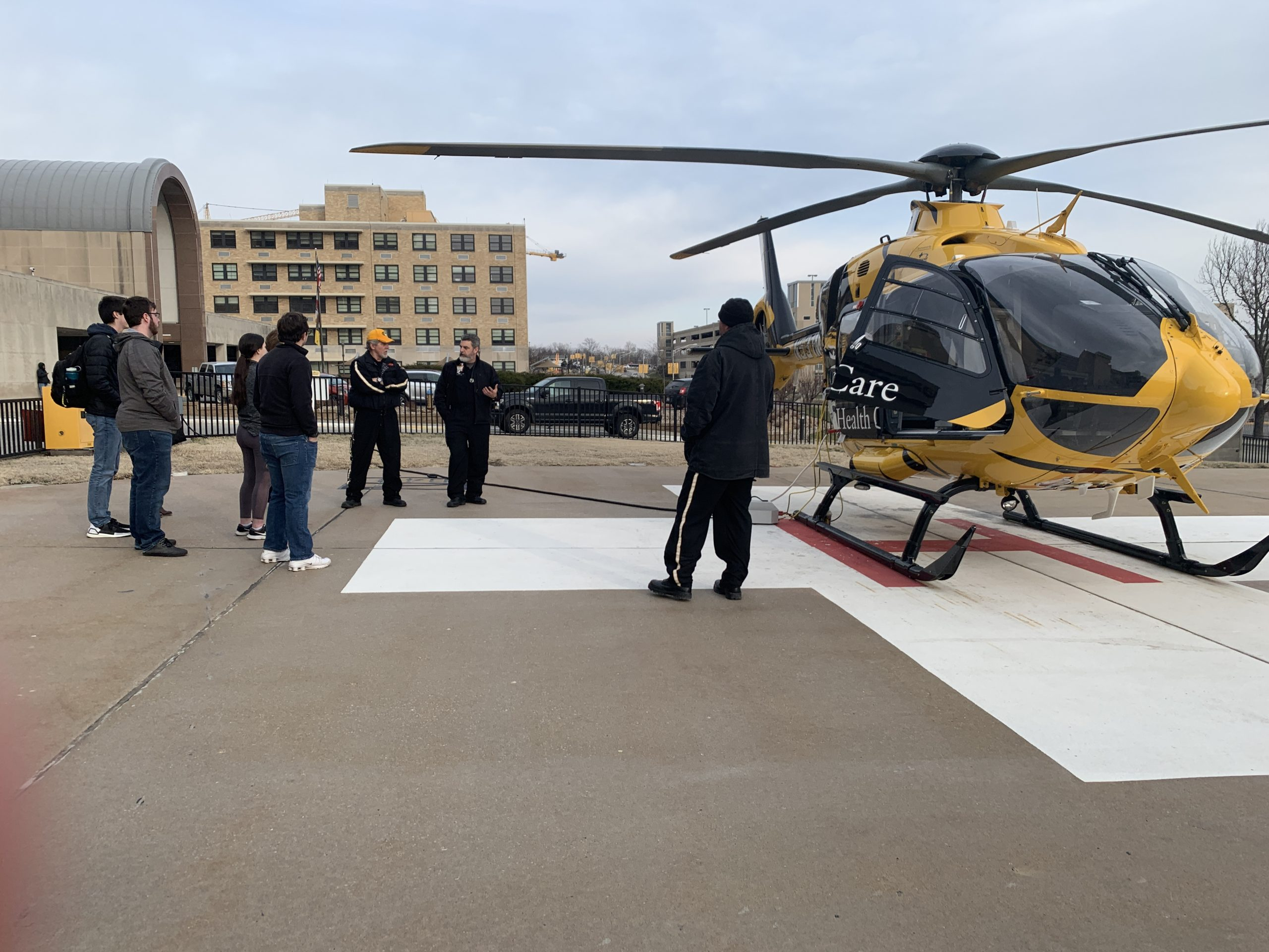 Students touring MU Health Care. This is a picutre of students learning about the ambulatory services as they stand next to the MU Health helicopter.