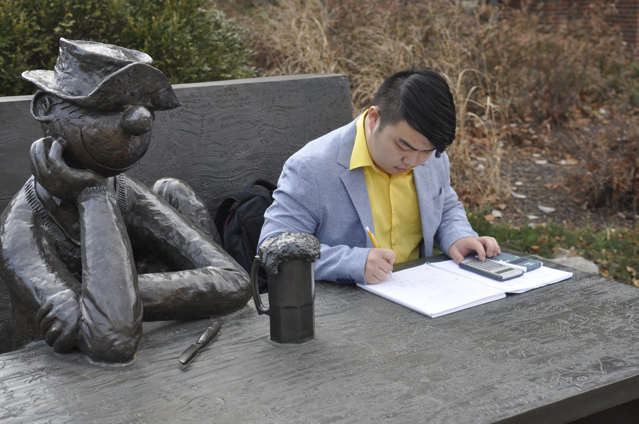 Xu works on math homework sitting at the Beetle Bailey statue