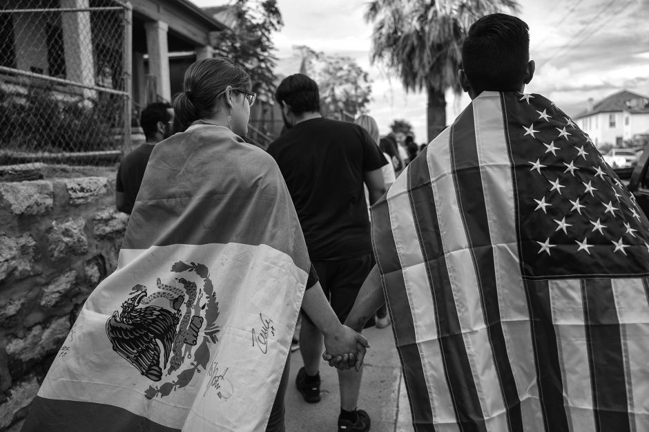 Hundreds of people, including a couple draped in Mexican and American flags, marched through central El Paso on August 2, 2019 in a protest against gun violence, in the wake of the Walmart terrorist attack. The Latino communities of El Paso and Ciudad Juarez were horrified to learn that the killer, who gave himself up for arrest, was specifically targeting Latinos and drove 600 miles to the Walmart where he gunned down scores of shoppers, killing 22.