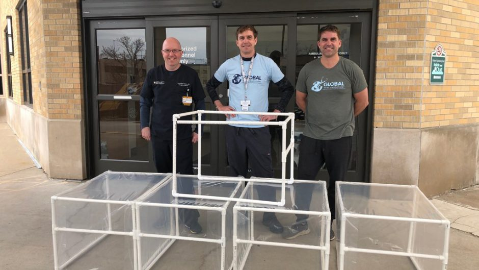A University Hospital employee (left) and the Beckett brothers with their respiration protection chambers.