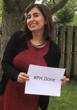 photo of student smiling and holding a sign that says #P.H. Done