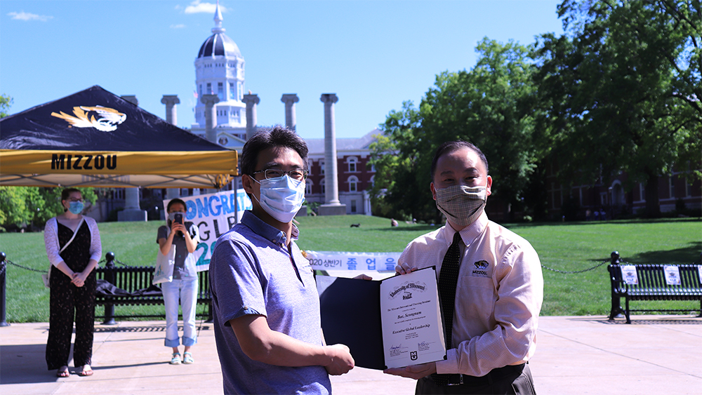 man handing another man a certificate in front of jesse hall