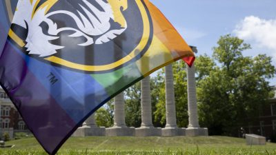 rainbow flag with mizzou tiger in front of columns