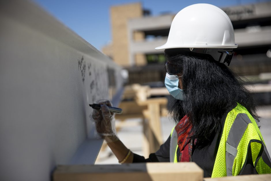 Provost Latha Ramchand adds her signature to the final beam of the NextGen Precision Health Institute. The beam was placed on June 18, 2020.