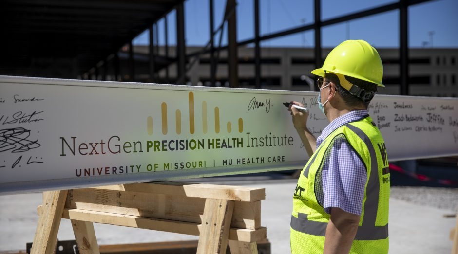 President and interim chancellor Mun Choi adds his signature to the final beam of the NextGen Precision Health Institute. The beam was placed on June 18, 2020.