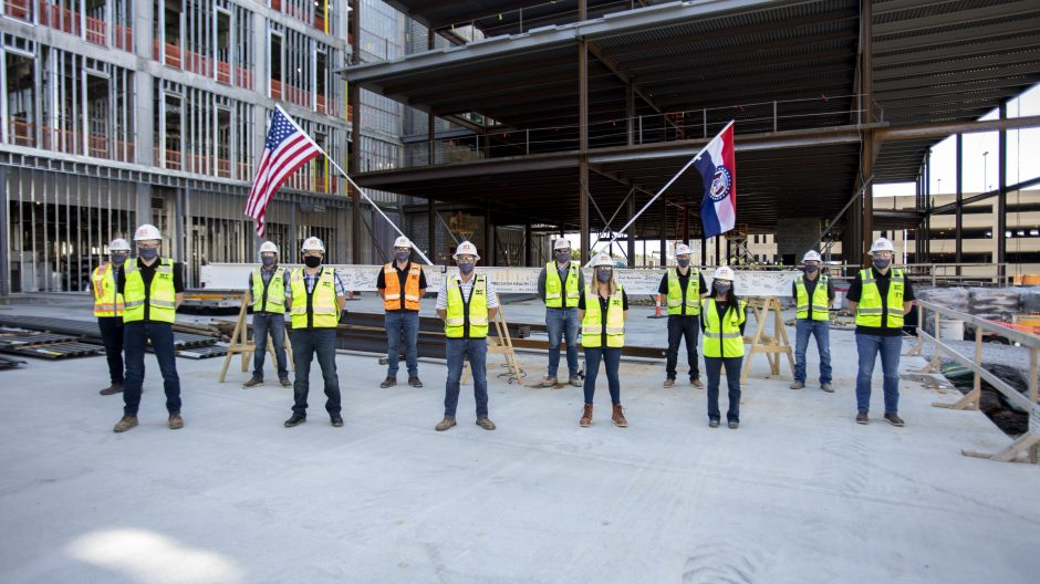 The construction team placed the U.S. and Missouri state flags on the final steel beam of the NextGen Precision Health Institute.