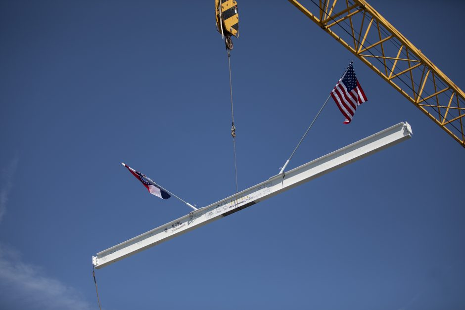 A crane lifts the final steel beam of the NextGen Precision Health Institute. The beam was installed on the top of the building during a virtual topping off ceremony on June 18, 2020.