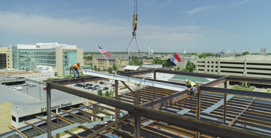 two men place the final beam atop the building