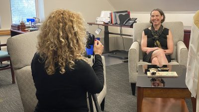woman sitting in a chair being filmed