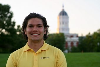student standing in front of jesse hall in yellow shirt