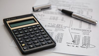This is an image of a pen and calculator on top of a sheet of paper with accounting information.