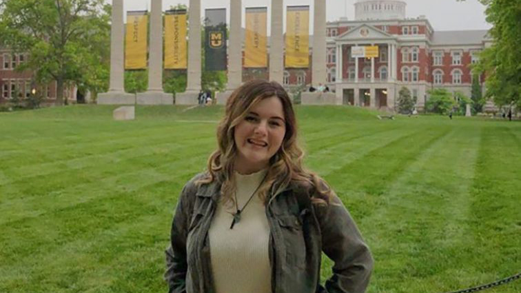 student in front of columns