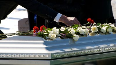 person laying flowers on a casket