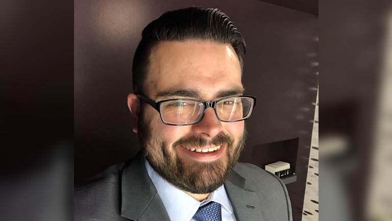 man with glasses and a beard in a suit smiling