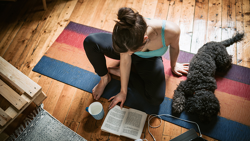 Young woman sitting on the carpet with her pet reading book and practicing yoga at the same time