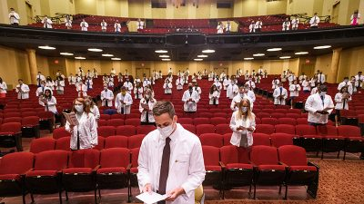 students in white coats, socially distanced, wearing masks and reading oath