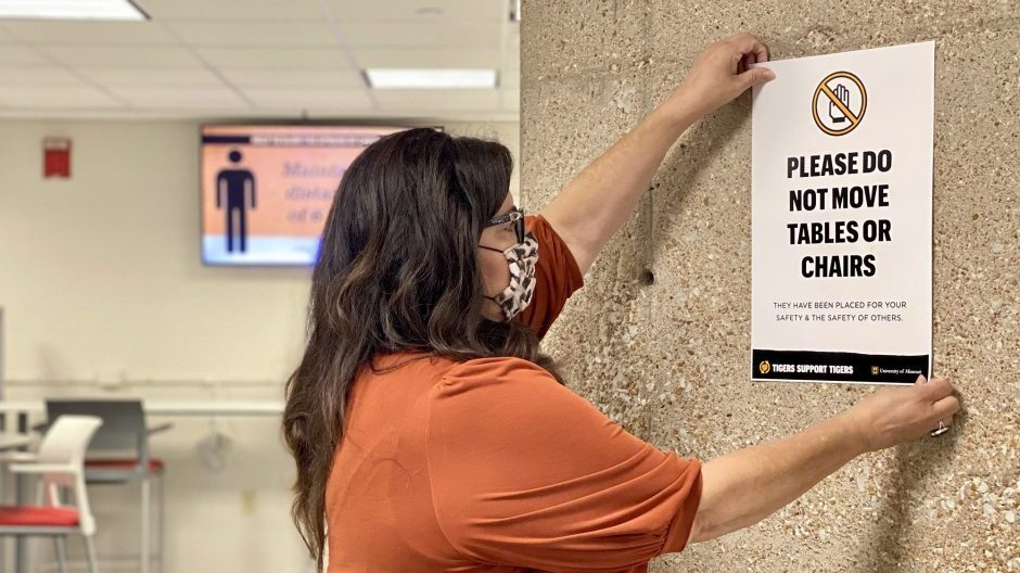 woman hanging a social distancing sign