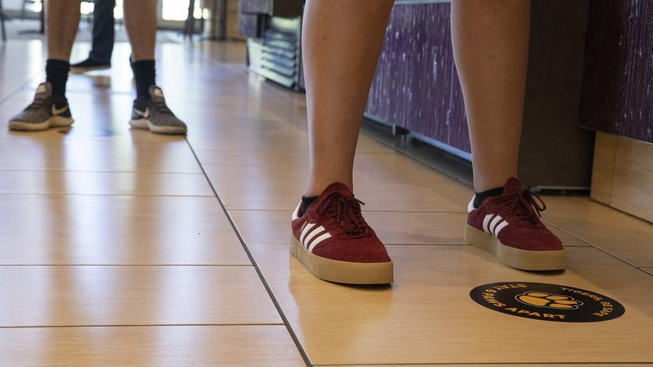student standing on a social distancing floor cling