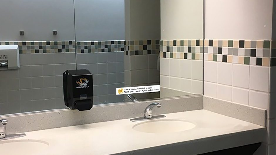 bathroom mirror with hand washing signage