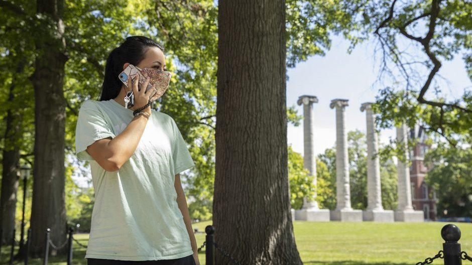 student near columns on her phone