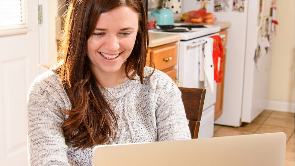 Woman using a laptop and tablet in her kitchen.