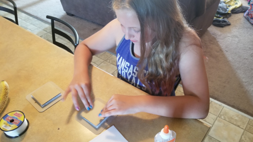 girl at table doing craft