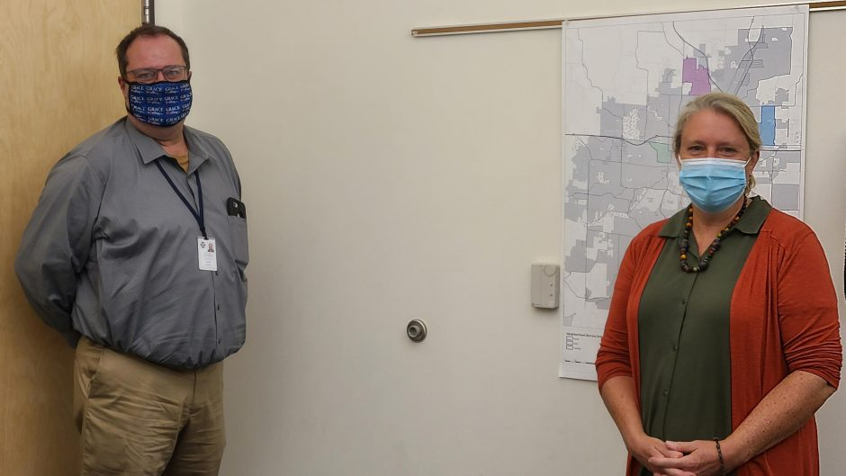 man and woman standing socially distanced wearing masks
