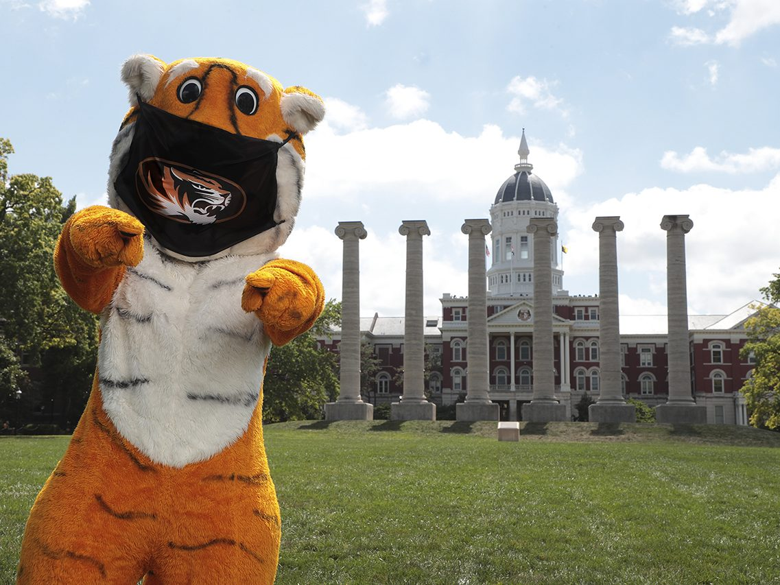 Truman the Tiger in a mask in front of Jesse Hall