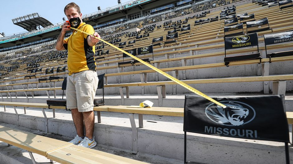 Man measuring distance of seats in Memorial Stadium