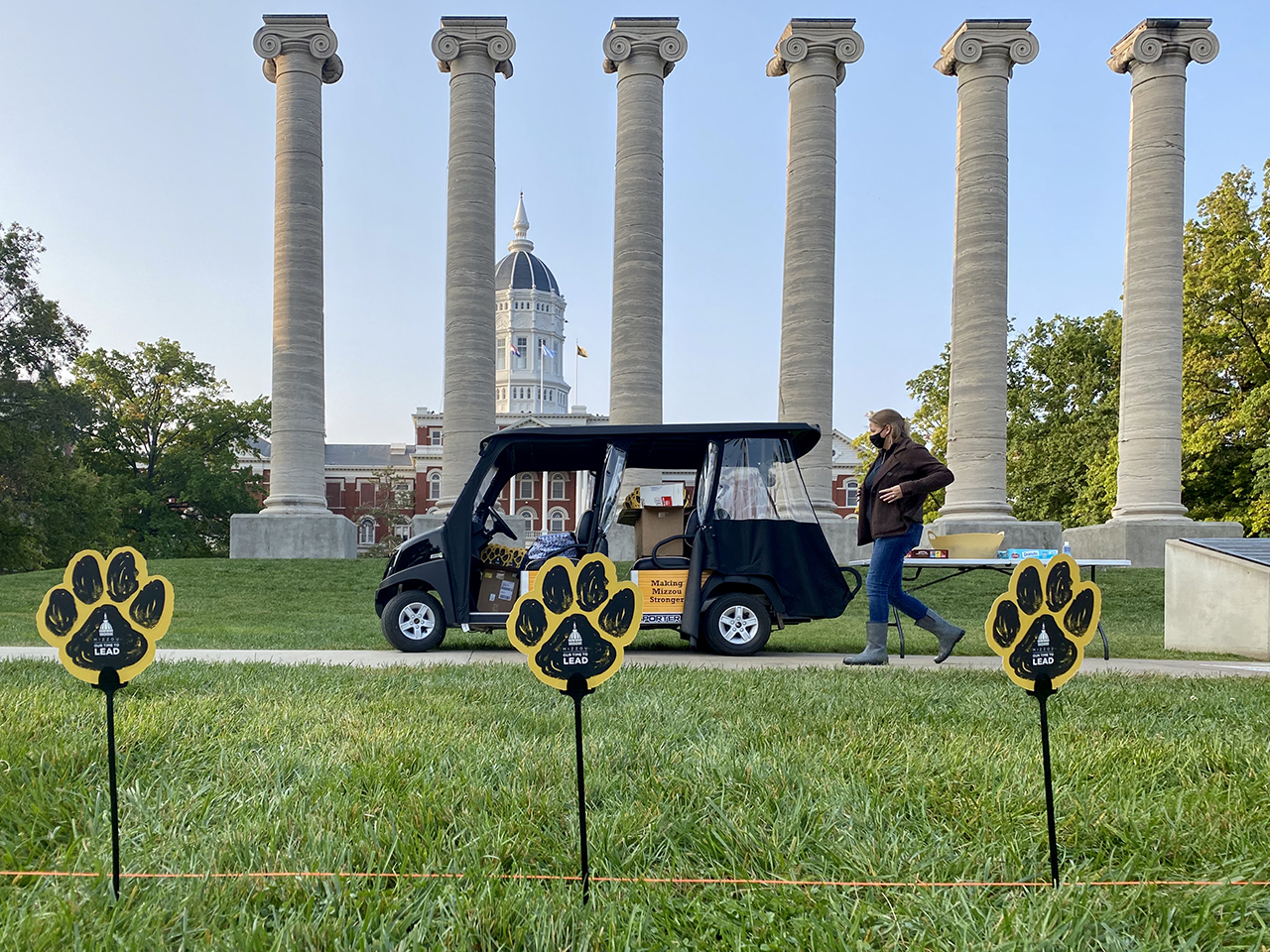 a woman walks in front of a golf cart with the columns in the background and paws on sticks in the foreground