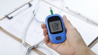 Hand holding a blood glucose meter measuring blood sugar, the background is a stethoscope and chart file