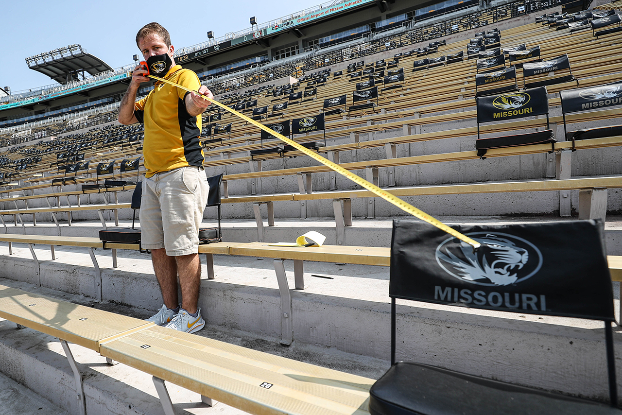 man with tape measure spacing out seats