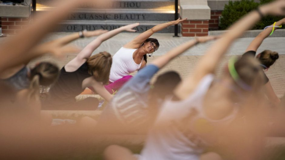 Student Affairs staff member, Andrea Kimura, leads a yoga class at Traditions Plaza in 2018.