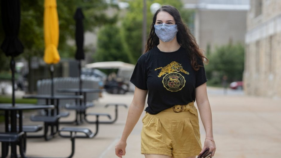 This is an image of a student walking outside of the student center with a mask.