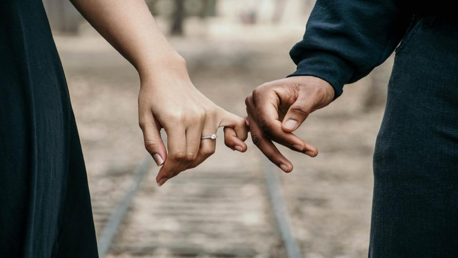 This is an image of an engaged couple holding hands.