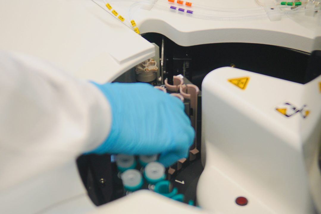 This is an image of a member of the research team placing blood samples into equipment provided by the Siemen's Healthineers.