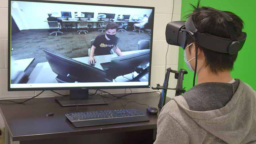 Weiyu Feng uses virtual reality goggles to experience a classroom he is not physically in. Through the goggles, he can see classmate Will Slama in a realistic setting rather than on screen.