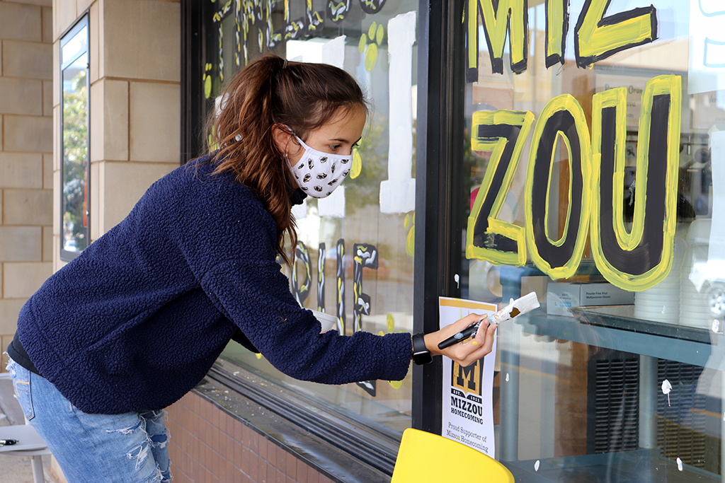 Students paint windows downtown as part of Decorate the District.