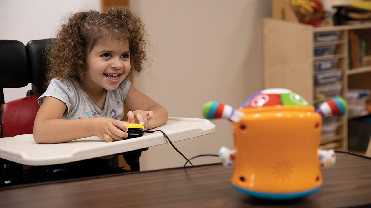 Claudia Stephens, 3, plays with Switched Adapted Toys at Children's Therapy Center.