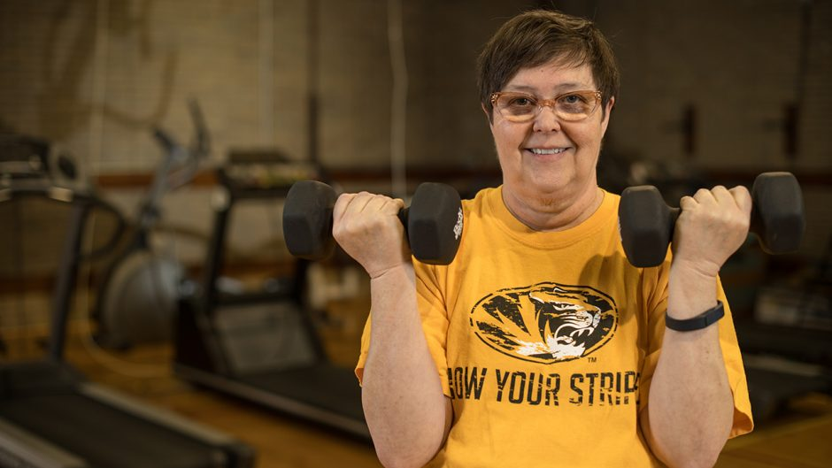 woman in a gold shirt smiling, lifting weights