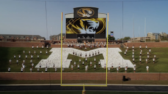 marching mizzou members stand socially distanced on the green grass and rock