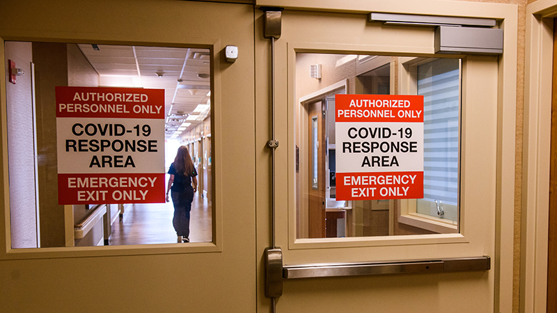 signs of the door of the COVID-19 unit within the Progressive Care Unit at University Hospital.