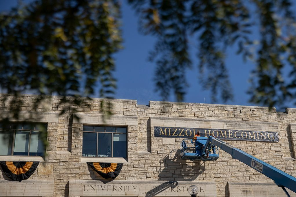 Campus facilities staff members install homecoming decorations at the Student Center.