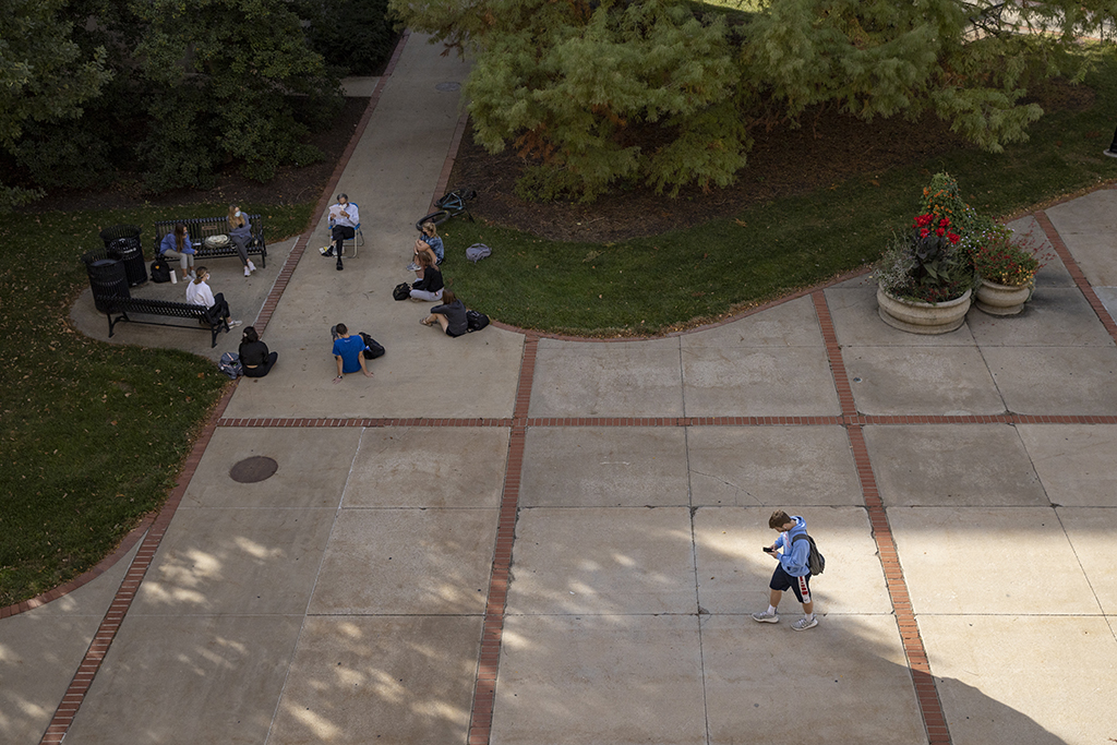students sitting socially-distanced outside