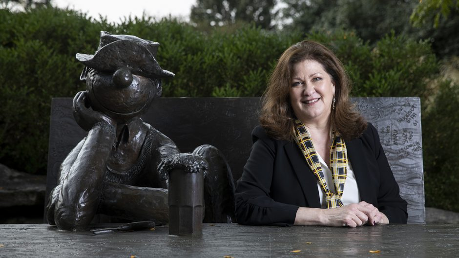 jackie lewis sits with beetle bailey bench statue