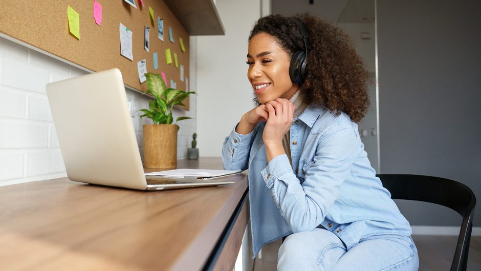 woman at a laptop with headphone on smiling
