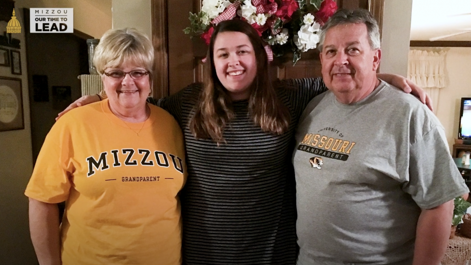 student in the middle with her grandparents on either side of her smiling
